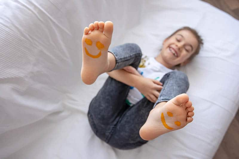 cute little girl smiling with smiley on her barefoot legs