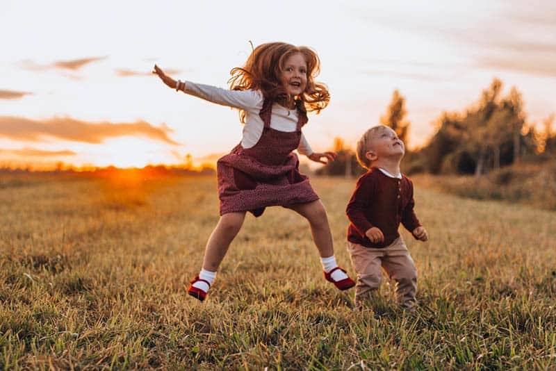cute little girl with brother jumping in the field