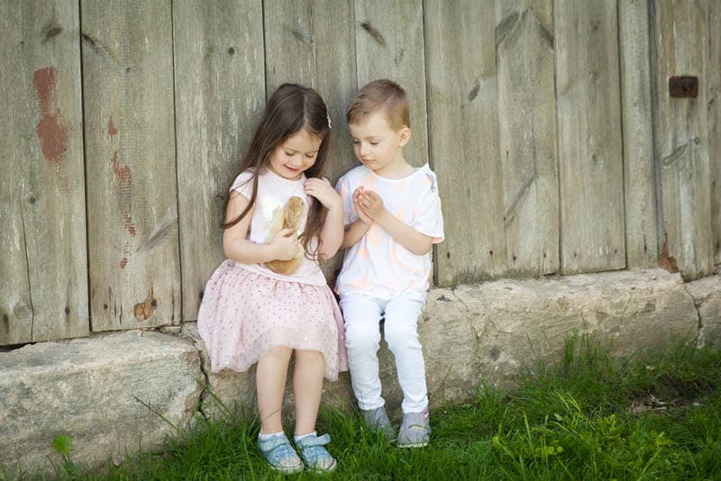 cute siblings playing with rabbit outdoor