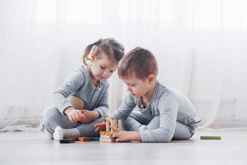 cute sister and brothet playing with toys on the floor