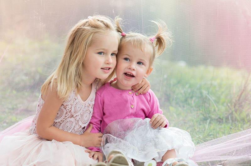 cute sister in pink dresses sitting in hug