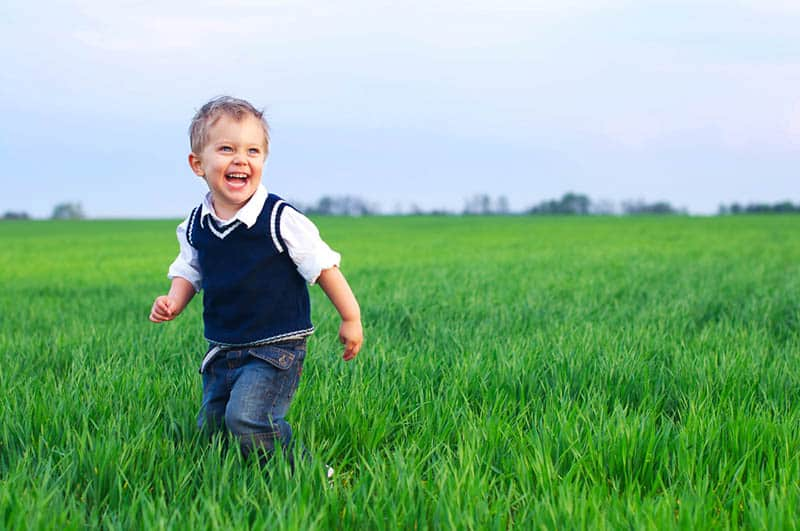 cute smiling boy running in the field