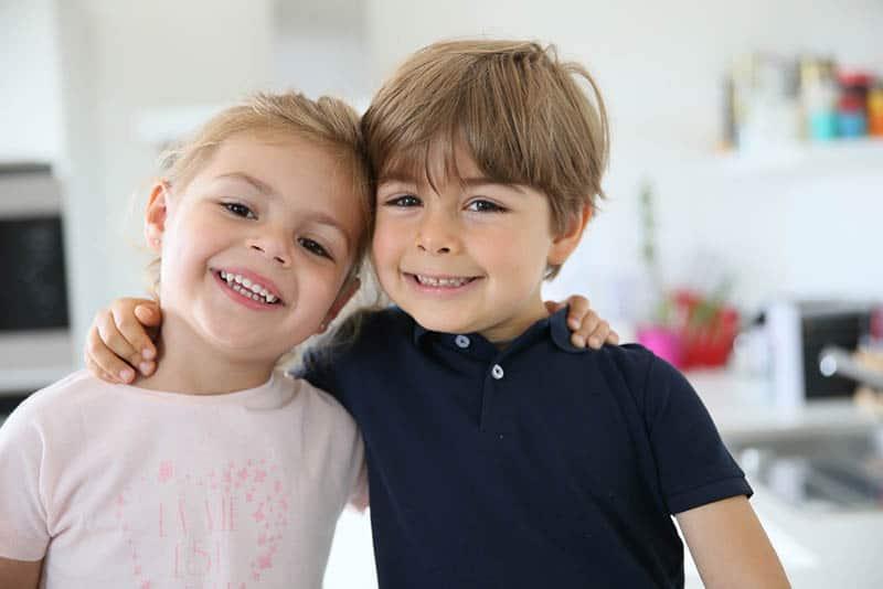 cute smiling siblings hugging at home
