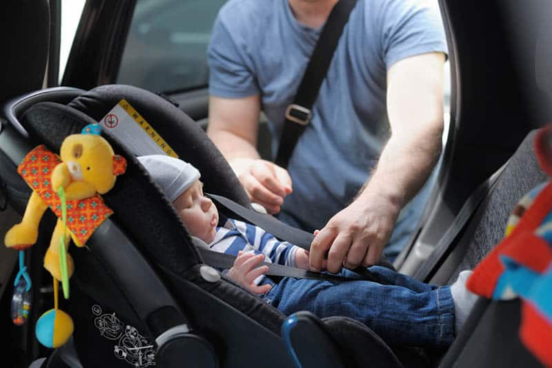 father fasting a security belt for baby in a car seat