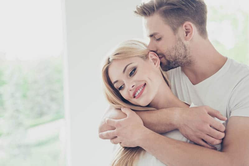 handsome man kissing his wife in head