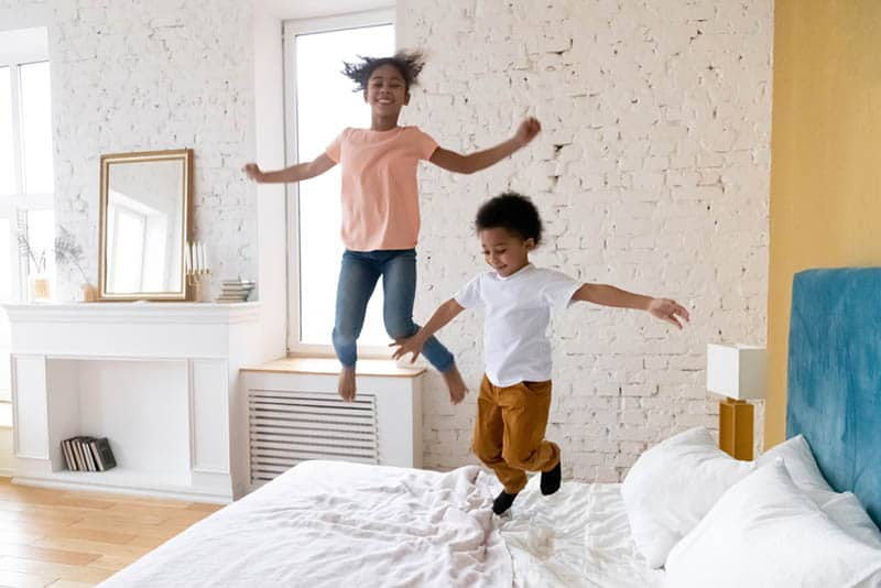 happy brother and sister jumping on the bed