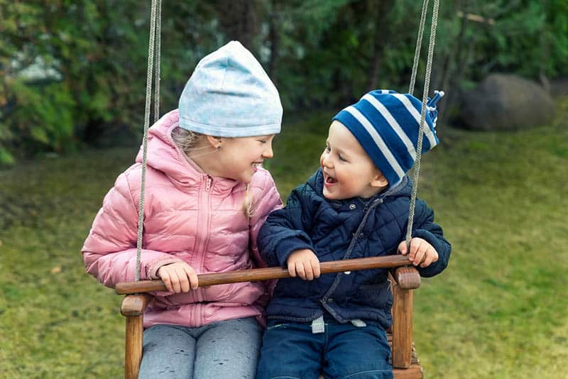 happy brother and sister swinging together in swingset