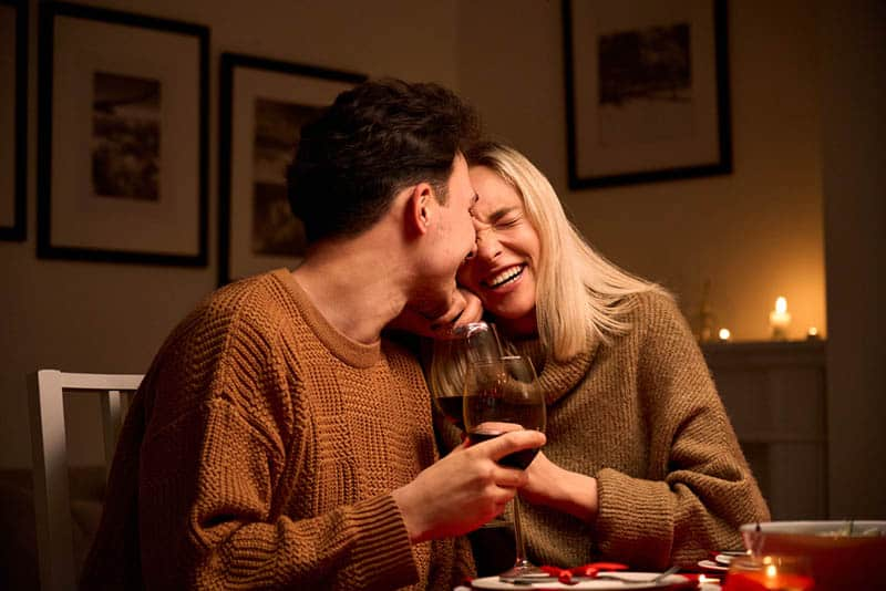 happy couple drinking wine on celebration at home with candles
