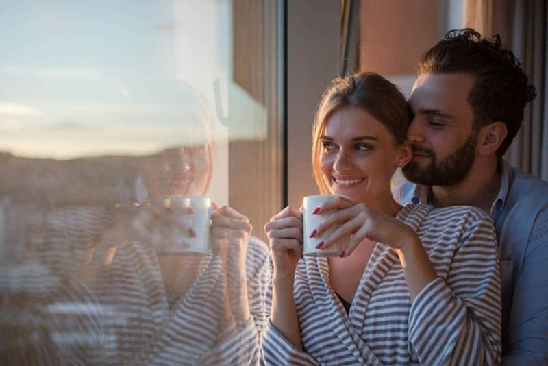 happy couple enjoying morning coffee by the window