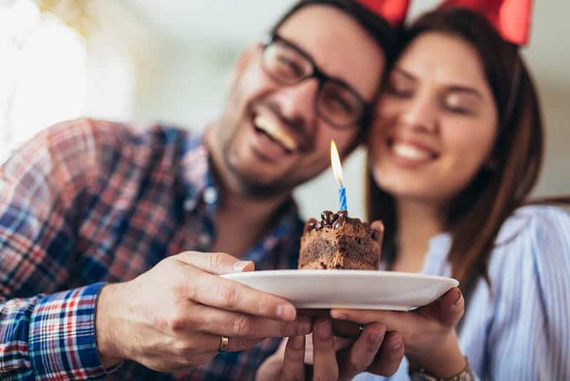happy couple holding a piece of cake with candle for birthday