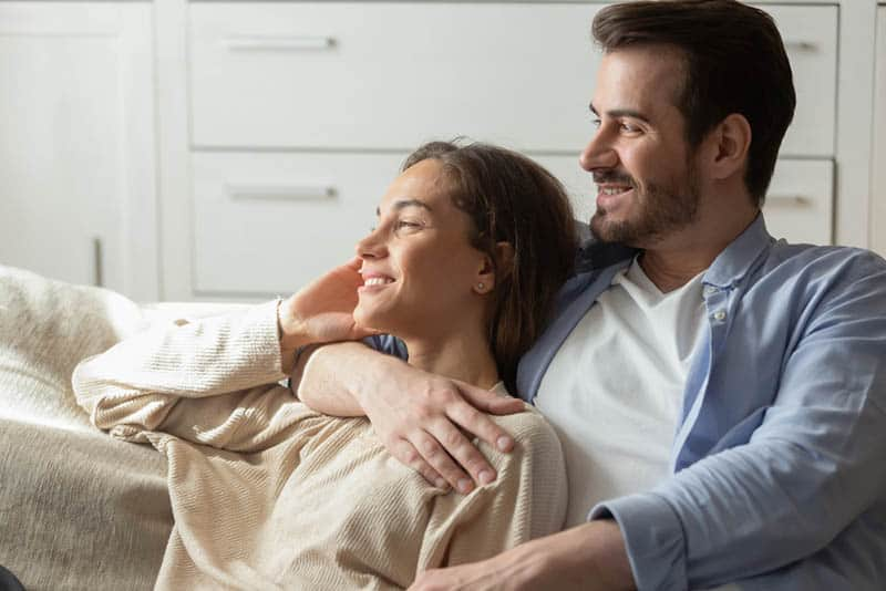happy couple lying on the couch in hug