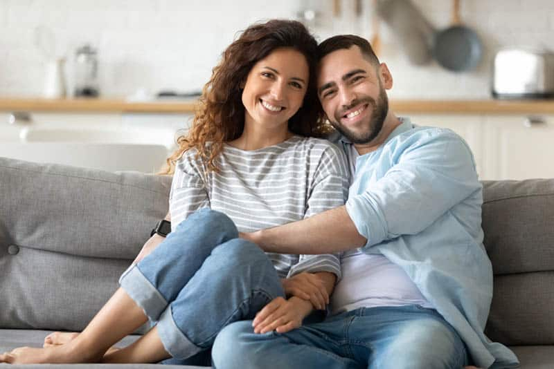 happy couple sitting in hug on the couch at home