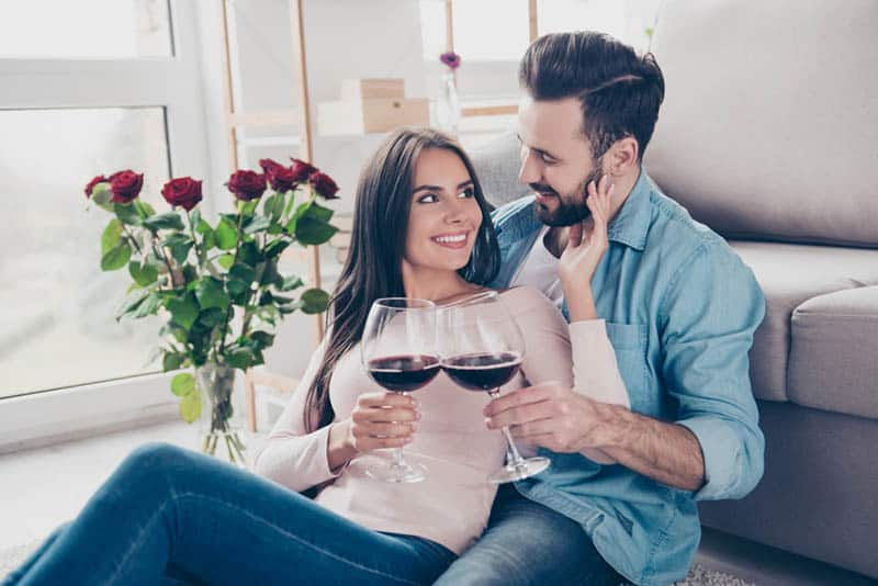 happy couple sitting on the floor and celebrating anniversary with wine