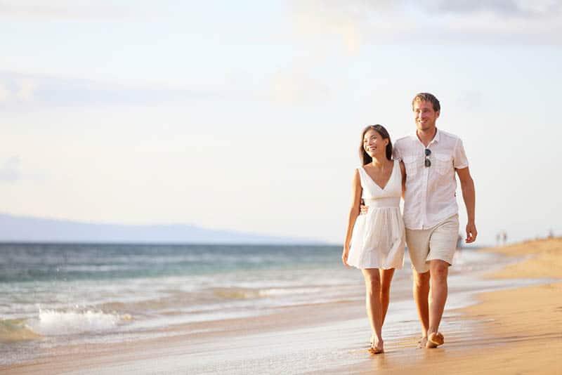 happy couple walking on the beach in hug