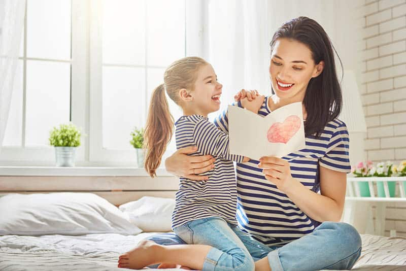 happy mother reading letter from her daughter for mother's day on the bed