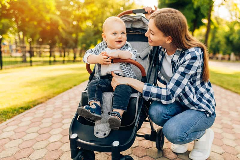 happy mother with baby in a stroller in the park