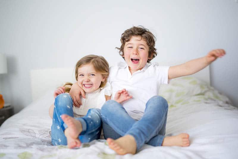 happy siblings hugging on the bed in bedroom