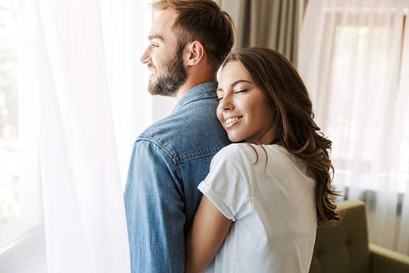 happy young woman hugging her husband at home