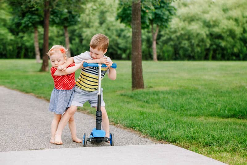 little boy pushing his sister from him in the park