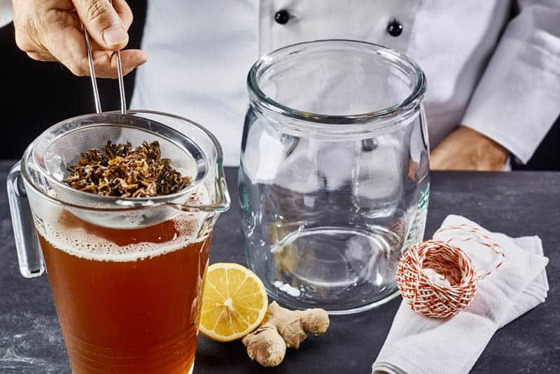 man preparing kombucha tea on the table