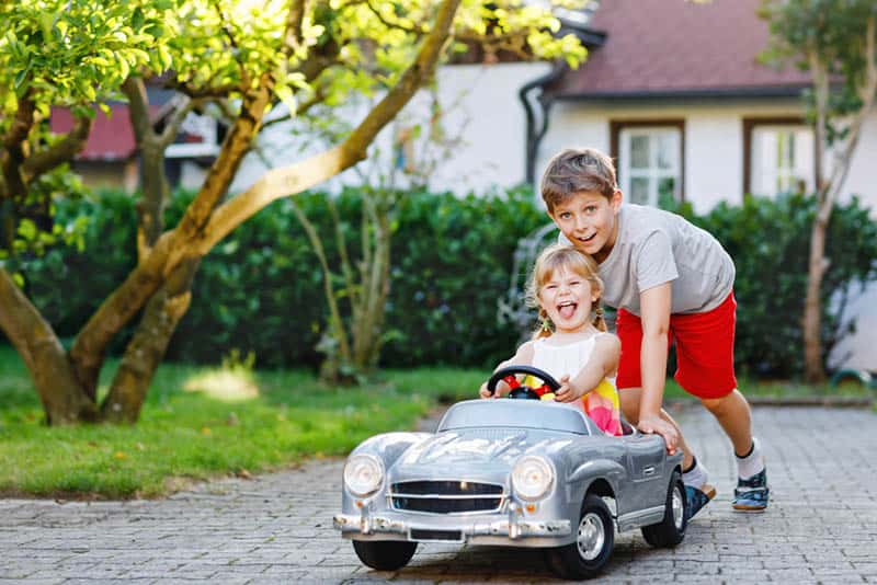 older brother playing with his sister in a car toy outdoor