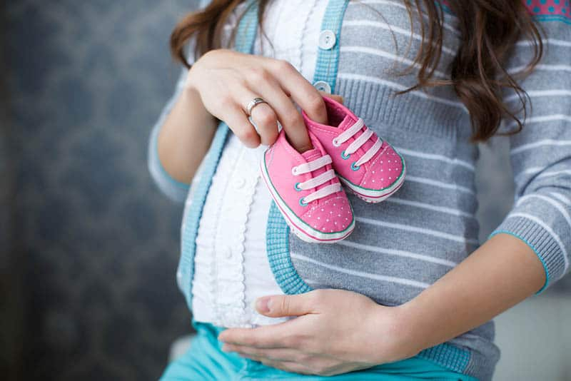 pregnant woman holding pink baby shoes
