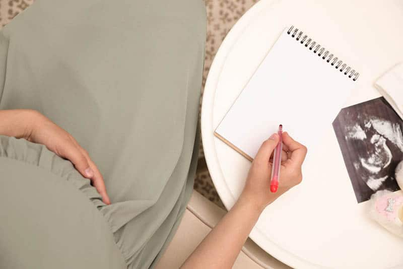 pregnant woman in dress writing on paper with sonogram picture on the table
