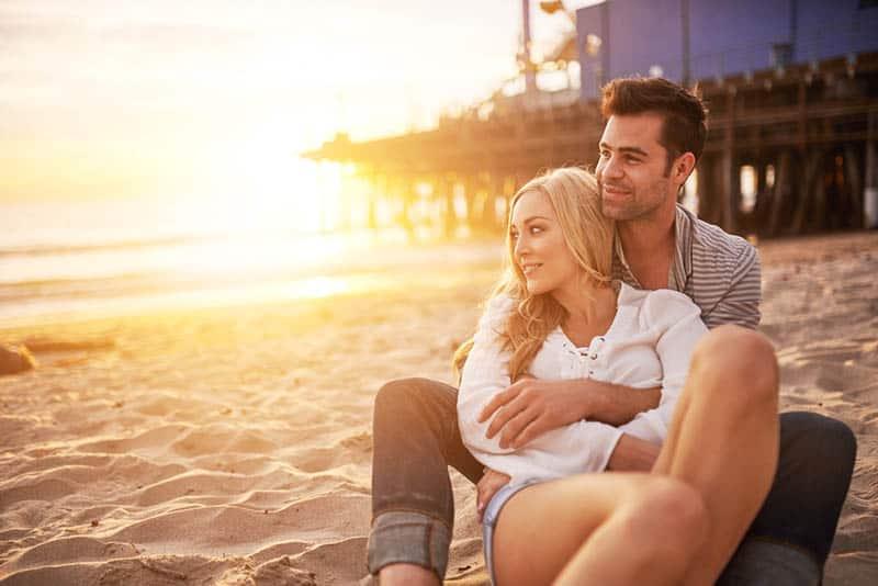 romantic couple enjoying sunset on the beach