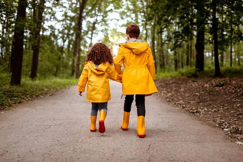 sisters in yellow raincoats holding hands and walking in the wood
