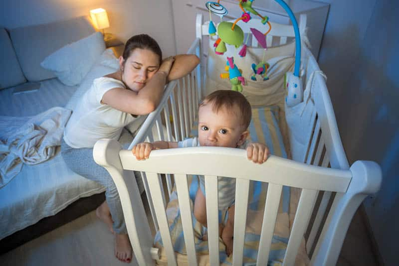 sleepless mother with baby in crib at night