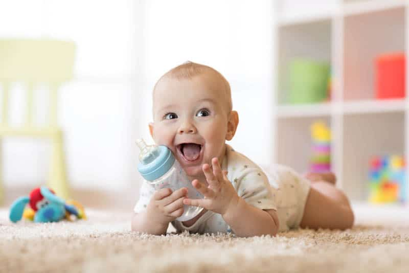 smiling baby with bottle on the floor laying