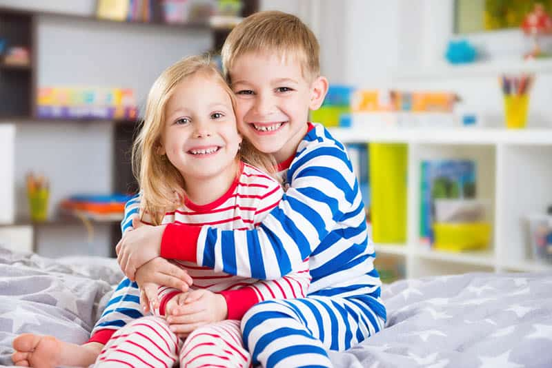 smiling brother with sister in hug wearing pajama on the bed