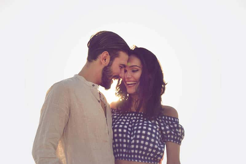 smiling couple standing outdoor together in hug