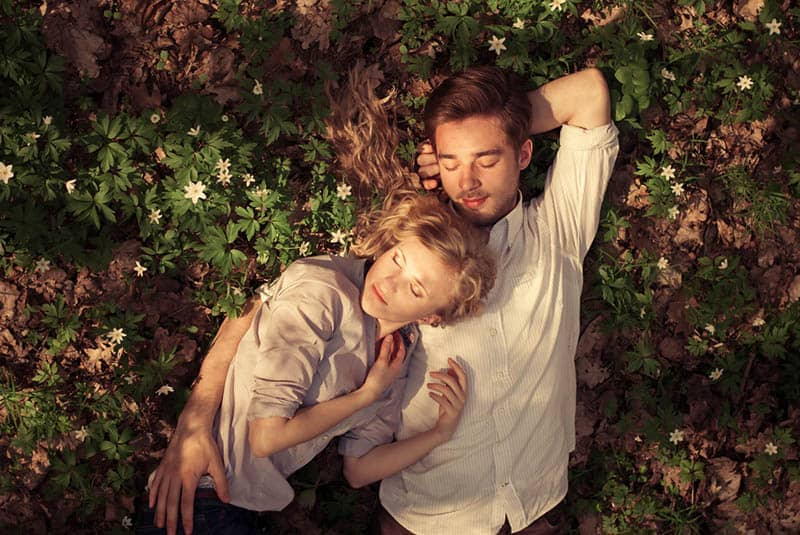 sweet couple lying on the grass between flowers