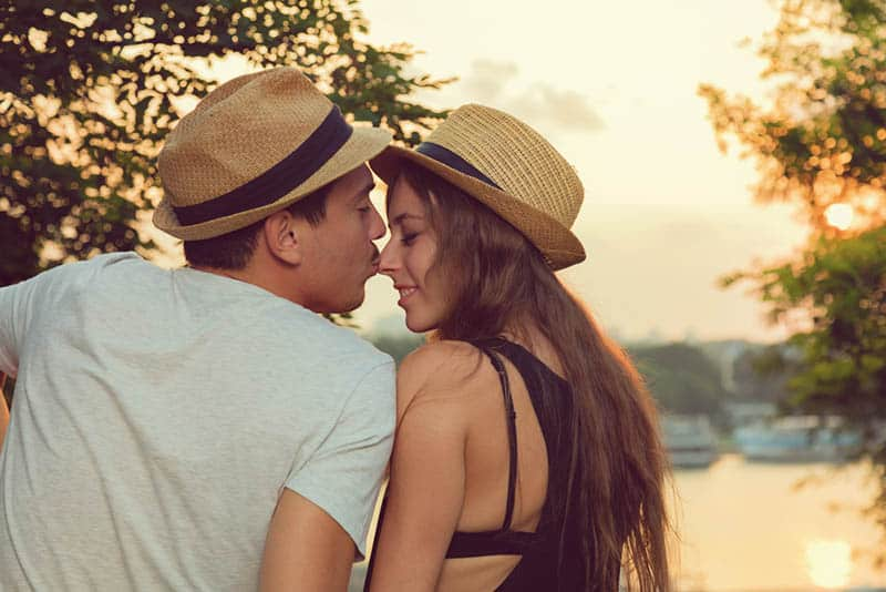 sweet man kissing woman's nose in the nature