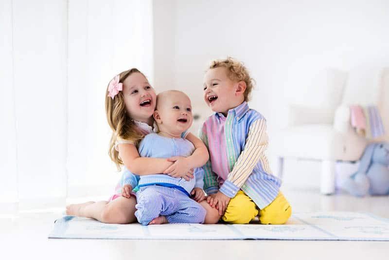 sweet siblings laughing and hugging on the floor
