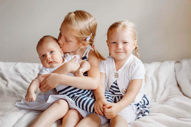 sweet sisters sitting with baby brother and kissing him