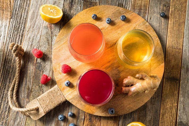 three glass of kombucha with fruits on the wooden board