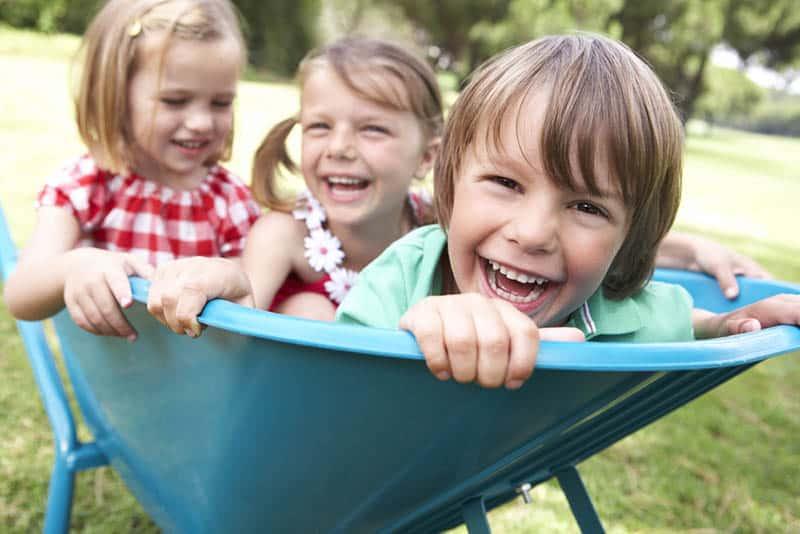 three happy kids sitting in a wheelbarrow on the grass outdoor