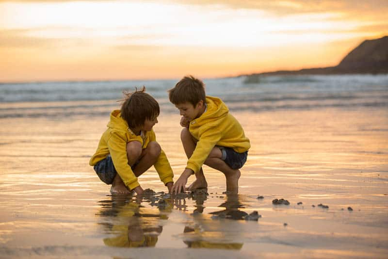 two boys playing in the sand on the beach