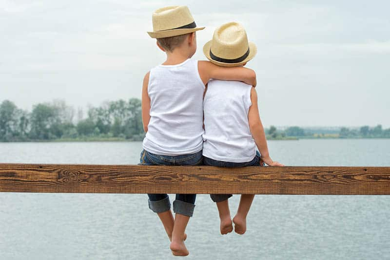 two brothers with hats sitting on the wood in front of the sea