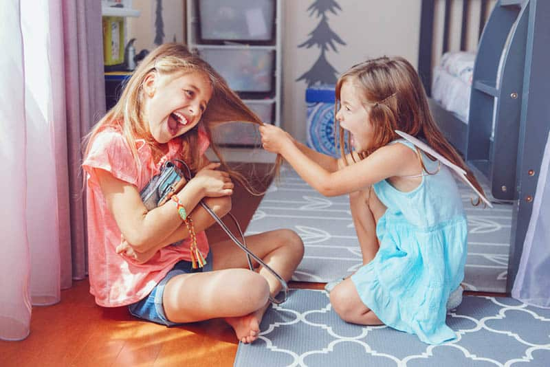 two cute sisters having fight at home on the floor