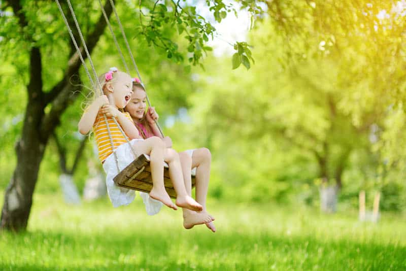 two cute sisters swinging together on the swingset in the park