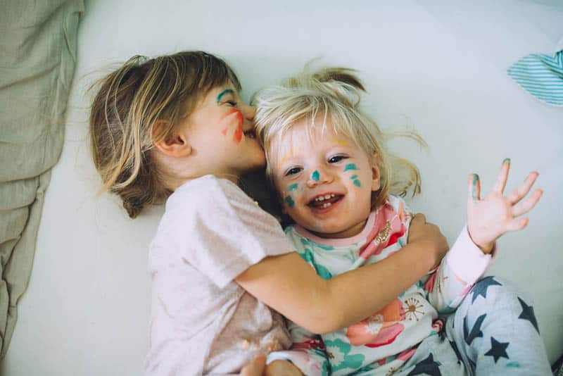 two little sisters with color on face laughing on the bed
