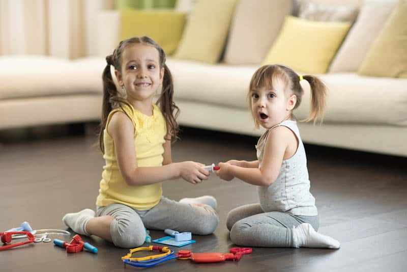two sisters playing on the floor with toys