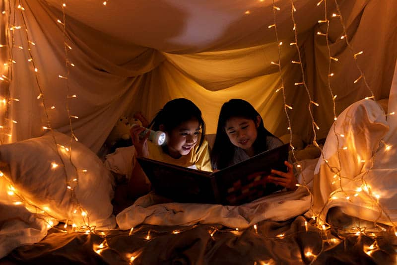 two sisters reading a book in a playing tent with flashlight