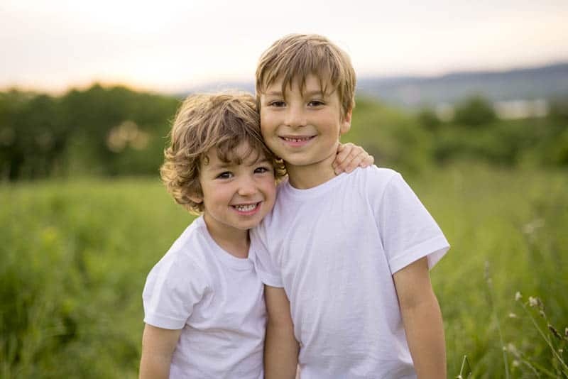 two smiling brothers hugging in the meadow
