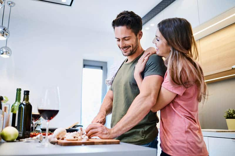 woman hugging man while he prepares food in the kitchen