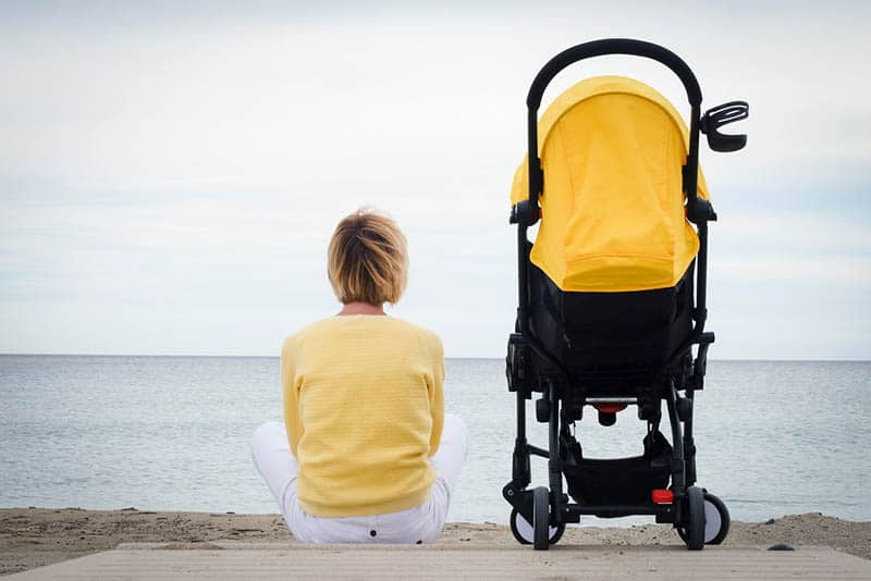 woman sitting on the beach with baby in a stroller