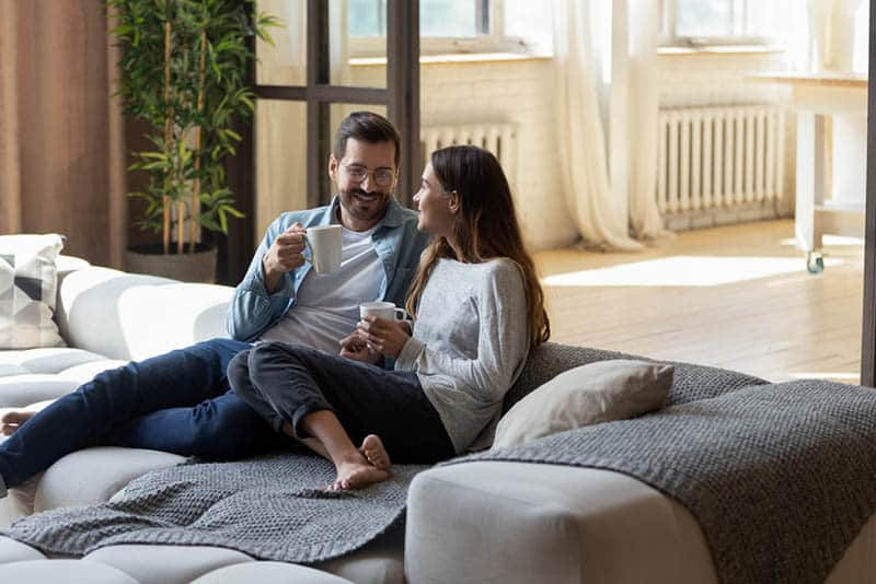 young couple drinking coffee on the huge couch at home